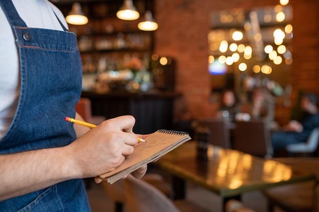 Рука молодого официанта в джинсовом фартуке держит карандаш над страницей блокнота, записывая заказ клиента на фоне интерьера