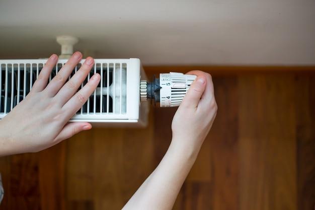 温度調節器でラジエーターの温度を変える若い女性の手