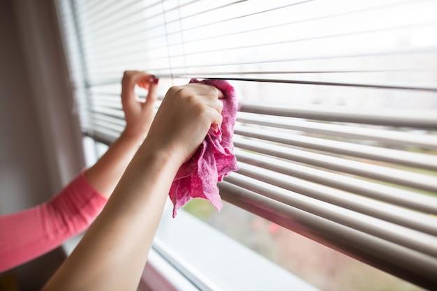 ピンクの布の家事でブラインドを掃除する若い女性の手、女性を掃除する