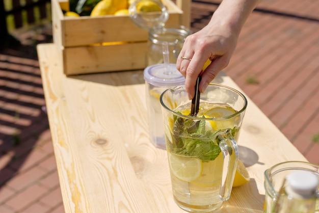 屋外の木の屋台のそばに立っている間ガラスの水差しで自家製レモネードの成分を混ぜる若い女性の手