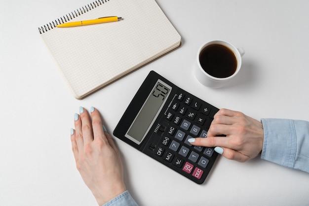 Рука молодой женщины используя калькулятор. концепция бюджетного планирования. белый фон, вид сверху