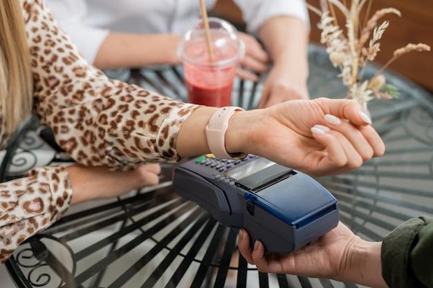 Рука молодой женщины с умными часами оплачивает напитки в кафе с помощью бесконтактной оплаты своим запястьем над терминалом pos