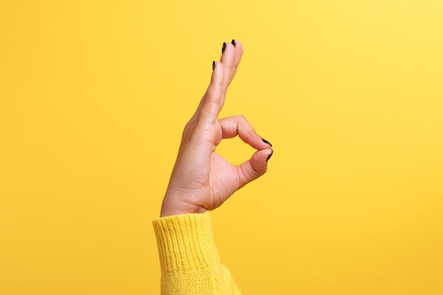 Рука ок знак на желтом фоне тенденции