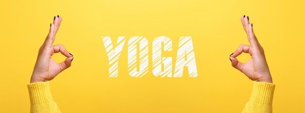 Hand ok sign with yoga inscription over trendy yellow background, panoramic image