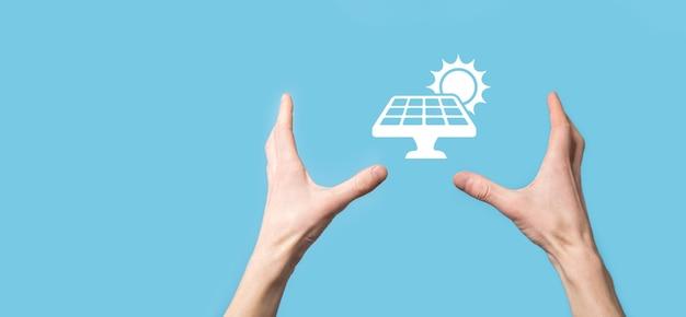 파란색 배경에 있는 손에는 태양 전지 패널의 아이콘 기호가 있습니다. 재생 에너지, 태양 전지판 스테이션 개념, 녹색 전기