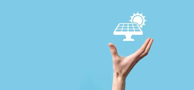 青い背景に手は、ソーラー パネルのアイコン シンボルを保持します。再生可能エネルギー、ソーラー パネル ステーションのコンセプト、グリーン電力。