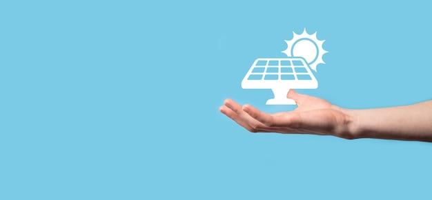 파란색 배경에 손은 태양 전지 패널의 아이콘 기호를 보유하고 있습니다. 신 재생 에너지, 태양 전지 패널 역 개념, 녹색 전기.