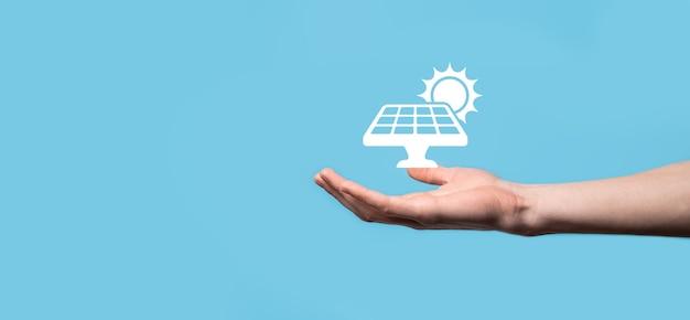 파란색 배경에 있는 손에는 태양 전지 패널의 아이콘 기호가 있습니다. 재생 에너지, 태양 전지 패널 스테이션 개념, 녹색 전기.