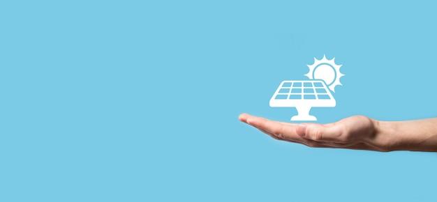 파란색 배경에 손은 아이콘 기호 태양 전지 패널을 보유하고 있습니다. 재생 에너지, 태양 전지판 스테이션
