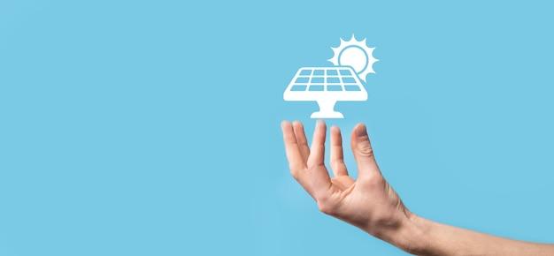 Рука на синем держит значок-символ солнечных батарей. возобновляемая энергия, концепция станции солнечных батарей
