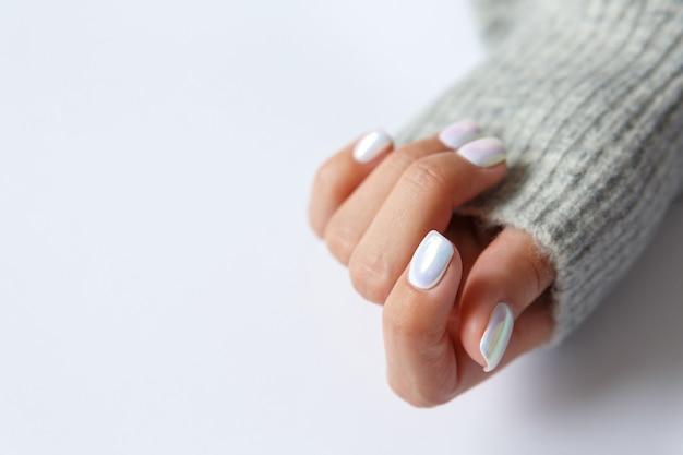 Рука на белом фоне и красивый жемчужный маникюр крупным планом