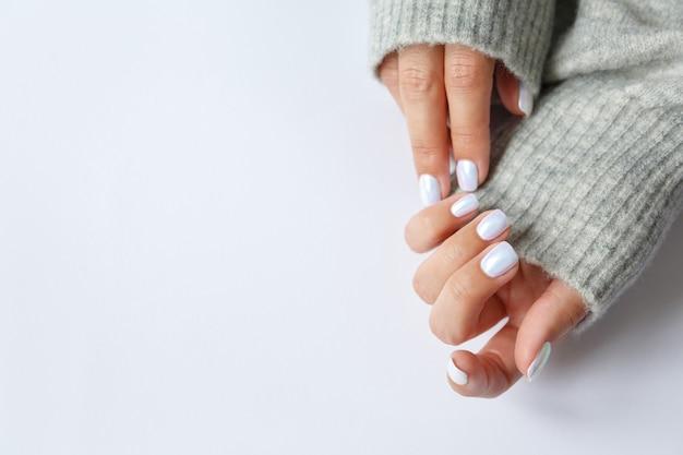 白い表面と美しい真珠のマニキュアのクローズアップを手に