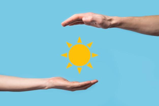 파란색 배경에 손을 잡고 태양 아이콘 기호를 보유하고 있습니다. 전기, 전원 공급 개념의 지속 가능한 소스입니다. 에코 환경 친화적인 기술 접근.