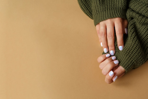 Рука на коричневом и красивом жемчужном маникюре крупным планом