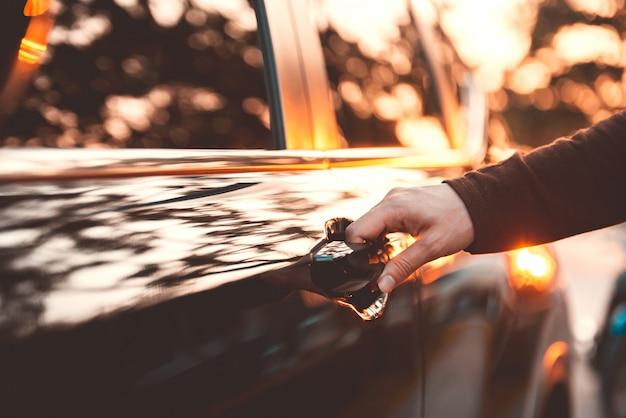 ハンドルを握ってください。日光の効果で車のドアを開く女性の手のクローズアップ。