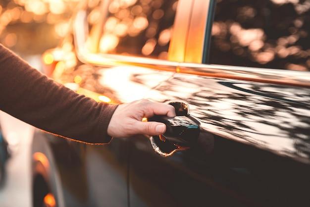 Рука на ручке. конец-вверх руки женщины раскрывая автомобильную дверь с влиянием солнечного света.