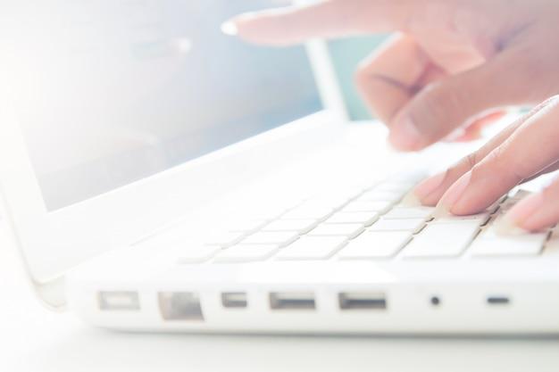 ノートパソコンのキーボードとポイントを手に、コピースペースのあるビジネスコンセプト
