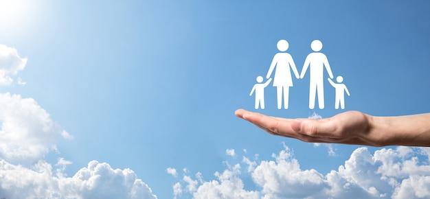 空の背景に手は家族のアイコンを保持します。ヘルスケアと生命保険の概念。父、母、娘、息子。