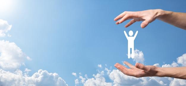 空の背景に手は人間のアイコンを保持します