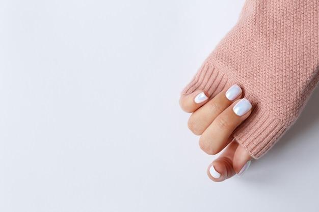 Рука на белом и красивом жемчужном маникюре крупным планом