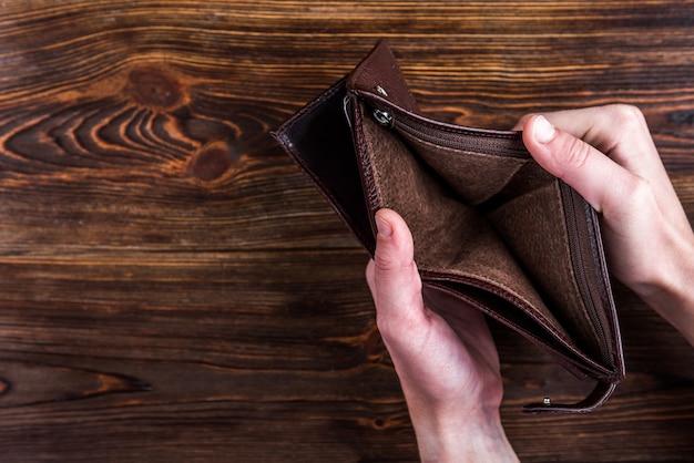 손으로 어두운 나무에 빈 지갑을 엽니 다.