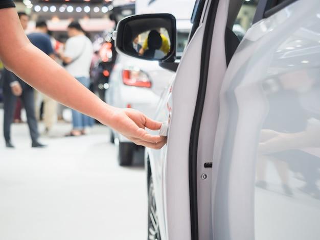 Рука открытая дверь автомобиля белого цвета и концепция автосалона