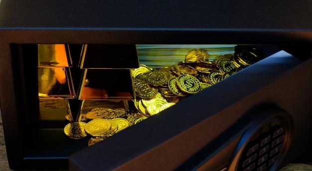 コインスタックとゴールドバーでいっぱいの手で開く電子機器のスチール製金庫