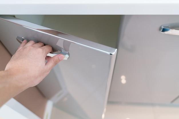 Hand open kitchen cabinet