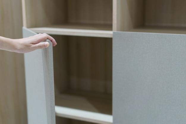 食器棚のドアを手で開き、茶色と白のキャビネットを開きます