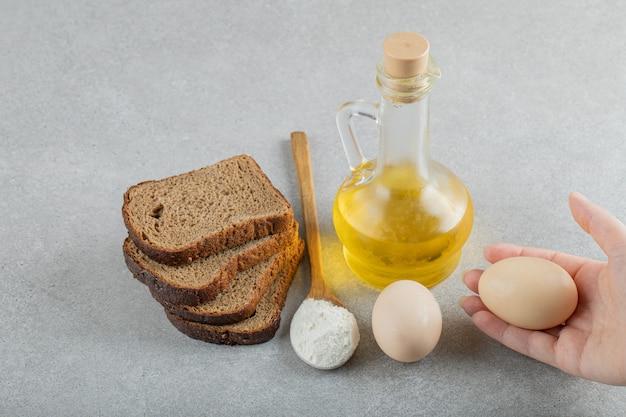 Рука открывает стеклянную бутылку масла с ломтиками хлеба.