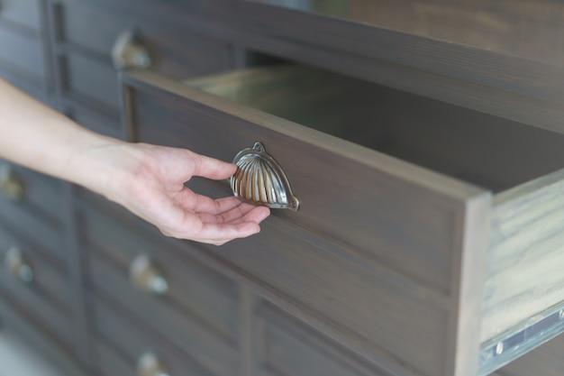 Рука, открывающая коричневые деревянные ящики для картотек.