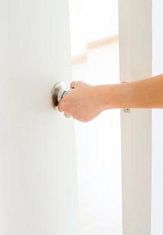 手のドアのノブ、白いドア