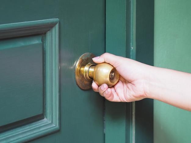 Hand opening green vintage door