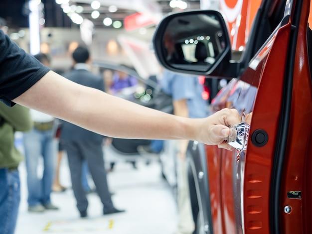 Рука, открывающая дверь автомобиля с фоном концепции автосалона
