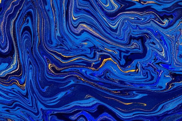 손으로 혼합 된 액체 파란색과 황금색 페인트로 배경을 그렸습니다.
