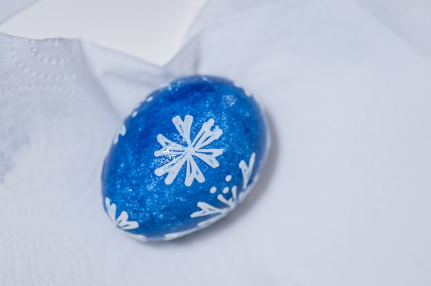 Hand painted blue easter egg on white paper napkin.