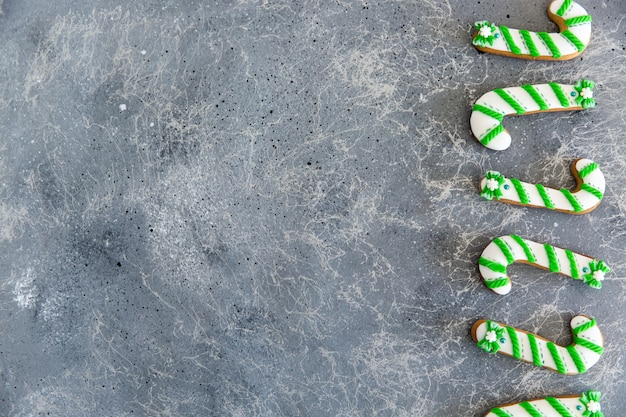 Hand painted christmas gingerbread green and white candy cane on a beautiful grey background. Premium Photo