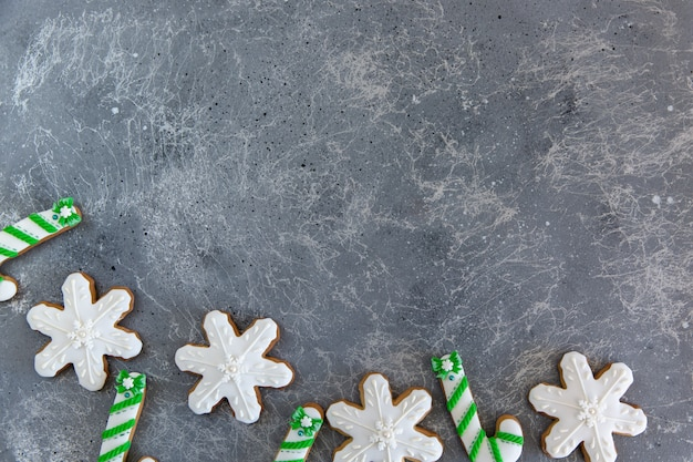 Hand painted christmas gingerbread green and white candy cane and snowflakes on a beautiful grey background.