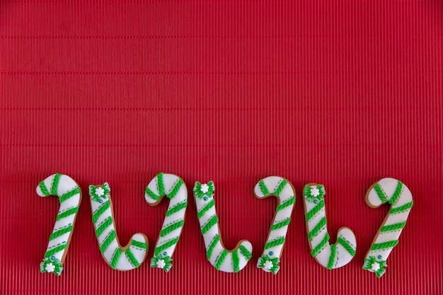 Hand painted christmas gingerbread green and white candy cane and snowflakes on a beautiful red background. card concept. top view. flat lay.