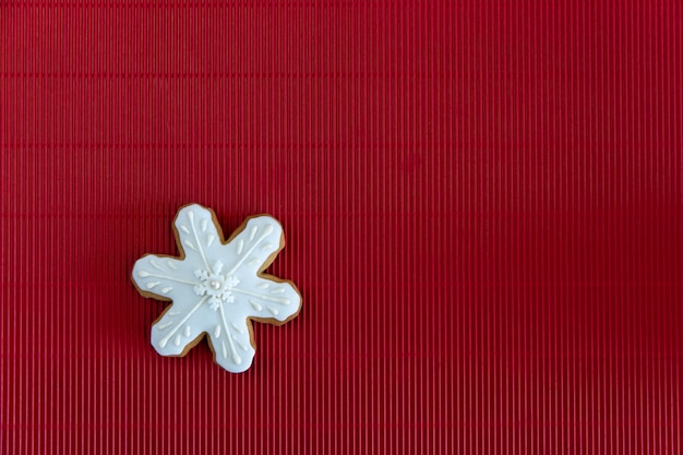 Hand painted christmas gingerbread white snowflake on a red corrugated background. card concept. top view. flat lay.