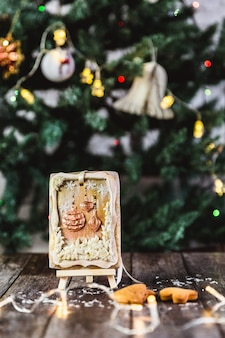 Hand painted christmas gingerbread on a wooden stand with abstract bokeh . close-up.