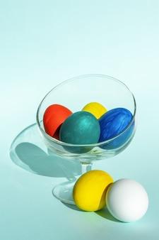 밝은 파란색 배경에 투명 유리 그릇에 손으로 그린 다채로운 부활절 달걀