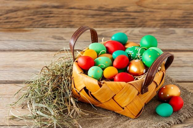 흰색 나무 배경에 바구니에 손으로 그린 장식된 부활절 달걀을 닫습니다. 부활절 배경입니다.