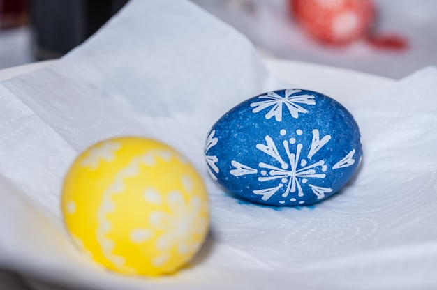 Hand painted easter egg on white paper napkin. the process of painting eggs with wax.
