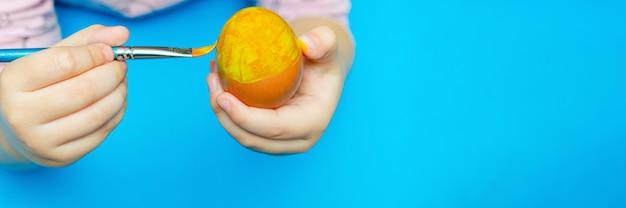 부활절 전에 손으로 그린 부활절 달걀. 파란색 배경에 부활절을 준비합니다. 여러 가지 빛깔된 페인트, 복사 공간입니다.