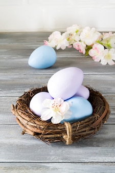 Hand-painted easter eggs in a nest with spring flowers on a wooden gray wall. happy easter
