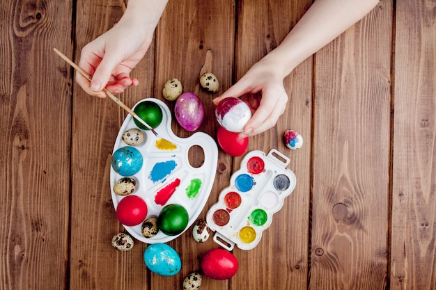 Hand painted easter eggs, paints and brushes on wooden background. preparation for the holiday. girls hands draw a pattern