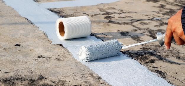 Покрашенный вручную серый пол с малярными валиками для водонепроницаемой армирующей сетки