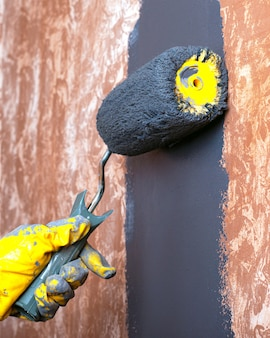 Hand painted home wall with gray acrylic paint with a roller in yellow work gloves.