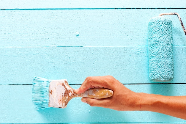 Hand painting blue color on white wooden plank
